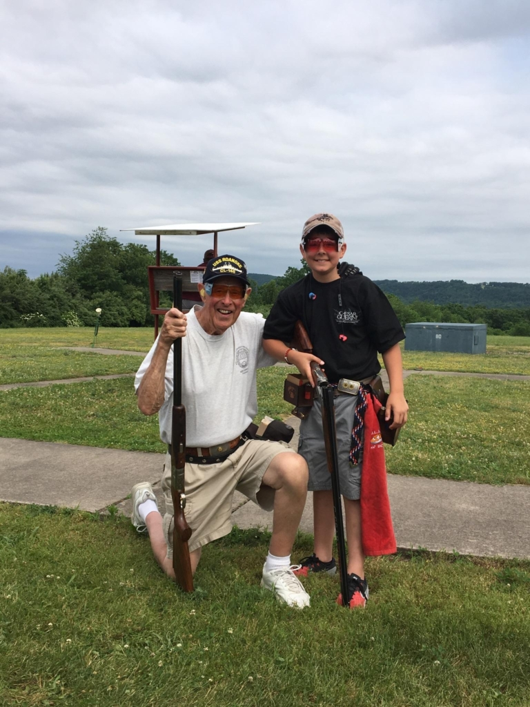 "Eleven-year-old Joseph Breck IV broke his first 100 during the class singles at the Pennsylvania State Shoot. Bob Mitchell is his squadmate and mentor. According to ATA Alternate Delegate Steve Ross (not pictured), ""It's a bit of a blend of old and new. Bob has over 575,000 singles targets, and Joe has 7,000. But the kid loves to shoot with the 'old man.' """