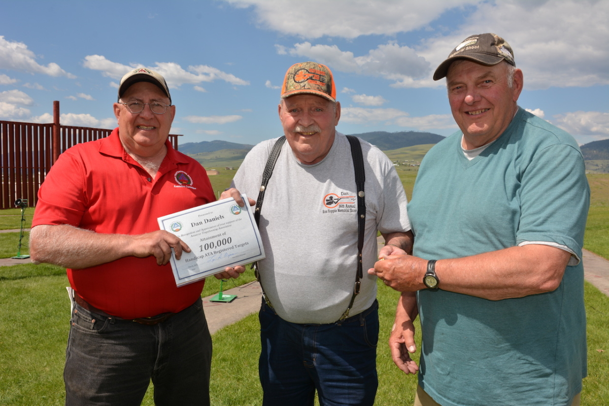 Dan Daniels (center) shot at and broke his 100,000th ATA handicap target Sunday at the Ron Hoppie Memorial tournament in Missoula, MT. Congratulating him and presenting his certificate were ATA President Jim Jones and ATA Past President Gene Clawson. See Hoppie shoot results this issue. (photo by Mark Kurruk)