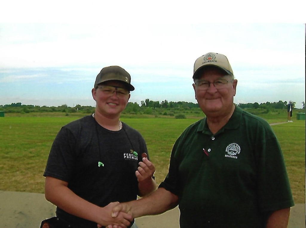 Clay Laughlin received his 27-yard pin from ATA Delegate Tim Deister. He earned his punch to the back fence for a 98 in the Grand's Clever Ammunition Handicap, where he was junior champ.